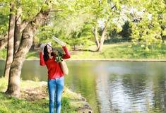 Η ασιατική κινεζική όμορφη στάση γυναικών από τον ποταμό κρατά μια ένδυση βιβλίων ένα καπέλο στη φύση την άνοιξη υπαίθρια Στοκ φωτογραφίες με δικαίωμα ελεύθερης χρήσης