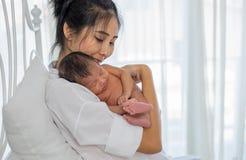 Η ασιατική λευκιά μητέρα πουκάμισων την κρατά λίγο νεογέννητο μωρό ύπνου στο στήθος της και κάθεται στο άσπρο κρεβάτι μπροστά από στοκ φωτογραφίες με δικαίωμα ελεύθερης χρήσης