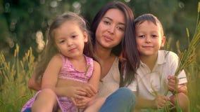Η ασιατική μητέρα με τα παιδιά κάθεται στον τομέα το καλοκαίρι, που κρατά τις συγκομιδές, προσέχοντας στη κάμερα, οικογενειακή έν απόθεμα βίντεο