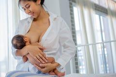 Η ασιατική μητέρα με το χαμόγελο δίνει το θηλασμό νεογέννητο με το άσπρο πουκάμισο και το κάθισμα στο άσπρο υπόβαθρο κρεβατιών τω στοκ εικόνα με δικαίωμα ελεύθερης χρήσης