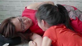Η ασιατική μητέρα παίζει με την κόρη της στο καθιστικό απόθεμα βίντεο