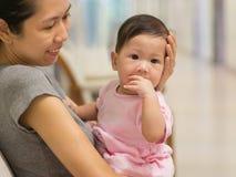 Η ασιατική μητέρα φέρνει το μωρό εσωτερικό Στοκ Εικόνες