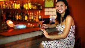 Η ασιατική νέα γυναίκα πίνει το κοκτέιλ μόνο στο φραγμό απόθεμα βίντεο