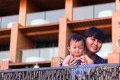 Η ασιατική νέα μητέρα και το χαριτωμένο εννέα μηνών μωρό απολαμβάνουν την πισίνα Στοκ φωτογραφίες με δικαίωμα ελεύθερης χρήσης