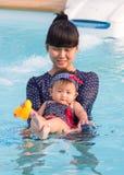 Η ασιατική νέα μητέρα και το χαριτωμένο οκτώ μηνών μωρό απολαμβάνουν την πισίνα Στοκ φωτογραφία με δικαίωμα ελεύθερης χρήσης