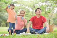 Η ασιατική οικογένεια φυσά τις φυσαλίδες σαπουνιών από κοινού στοκ εικόνες