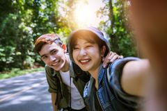 Η ασιατική ομάδα νέων με τους φίλους και σακίδια πλάτης που περπατούν μαζί και οι ευτυχείς φίλοι παίρνουν τη φωτογραφία και selfi στοκ φωτογραφία
