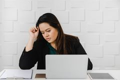 Η ασιατική παχιά επιχειρηματίας κάθεται αγωνιωδώς στο γραφείο στοκ εικόνα με δικαίωμα ελεύθερης χρήσης