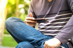 Η ασιατική συνεδρίαση ατόμων στον κήπο και εξετάζει το κινητό τηλέφωνο Στοκ Εικόνες