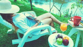 Η ασιατική συνεδρίαση γυναικών χαλαρώνει Διαβάστε τα περιοδικά και πιείτε το χυμό στον κήπο στοκ εικόνα με δικαίωμα ελεύθερης χρήσης