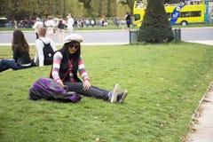 Η ασιατική ταϊλανδική γυναίκα κάθεται και θέτοντας στον κήπο χλόης για πάρτε τη φωτογραφία Στοκ εικόνα με δικαίωμα ελεύθερης χρήσης