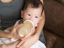 Η ασιατική τροφή μητέρων αρμέγει το μωρό της στο μπουκάλι στο σπίτι τους Στοκ φωτογραφία με δικαίωμα ελεύθερης χρήσης
