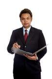 Η ασιατική υπογραφή σημαδιών επιχειρηματιών σε μια έκθεση εξετάζει τη κάμερα Στοκ Εικόνες