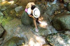 Η ασιατική φωτογραφία γυναικών παίρνει μια φωτογραφία του καταρράκτη στο βαθύ δάσος Στοκ Φωτογραφίες