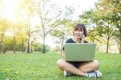 Η ασιατική χρησιμοποίηση γυναικών στο έξυπνο τηλέφωνο και το lap-top με το αίσθημα χαλαρώνουν και το πρόσωπο smiley Στοκ Εικόνες