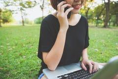 Η ασιατική χρησιμοποίηση γυναικών στο έξυπνο τηλέφωνο και το lap-top με το αίσθημα χαλαρώνουν και το πρόσωπο smiley Στοκ φωτογραφία με δικαίωμα ελεύθερης χρήσης