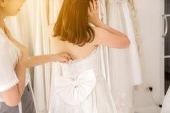 Η ασιατική όμορφη νύφη γυναικών που προσπαθεί στο γαμήλιο φόρεμα, γυναίκες προσαρμόζει τη διενέργεια της προσαρμογής στον πελάτη  στοκ εικόνες με δικαίωμα ελεύθερης χρήσης