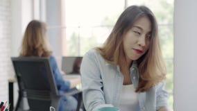 Η ασιατικοί δημιουργικοί μουσική και ο χορός ακούσματος επιχειρησιακών γυναικών μαζί, θηλυκό χαλαρώνουν μετά από να εργαστούν στο απόθεμα βίντεο