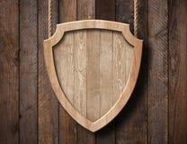 Η ασπίδα αμυντικής προστασίας διαμόρφωσε το σημάδι φιαγμένο από φωτεινό ξύλο και ένωση στα σχοινιά με το ξύλινο υπόβαθρο σανίδων στοκ εικόνα με δικαίωμα ελεύθερης χρήσης