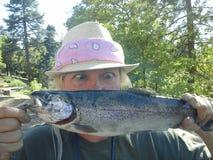 Η αστεία έκπληκτη γυναίκα πιάνει τα μεγάλα ψάρια Oncorhynchus mykiss στοκ εικόνες με δικαίωμα ελεύθερης χρήσης