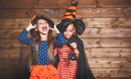 Η αστεία αδελφή παιδιών ζευγαρώνει το κορίτσι στο κοστούμι μαγισσών σε αποκριές στοκ εικόνες