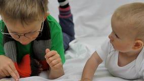 Η αστεία αλυσίβα αδελφών στην κοιλιά, μεγαλύτερος αδελφός με eyeglasses διάβασε το βιβλίο στο προσεκτικό μωρό απόθεμα βίντεο