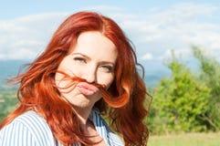 Η αστεία γυναίκα παρουσιάζει moustache τρίχα και κατοχή της διασκέδασης Στοκ Εικόνες