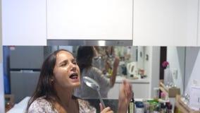 Η αστεία όμορφη νοικοκυρά γυναικών στις πυτζάμες cookes χορεύει και τραγουδά το τραγούδι με την κουτάλα μαγειρεύοντας στη σύγχρον φιλμ μικρού μήκους