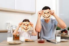 Η αστείοι όμορφοι κόρη και ο πατέρας κάνουν τα πρόσωπα με τις τηγανίτες, κάνουν τη διασκέδαση μαζί στην κουζίνα κατά τη διάρκεια  στοκ εικόνες με δικαίωμα ελεύθερης χρήσης
