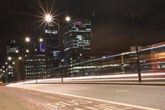 Η αστική νύχτα πόλεων πυροβόλησε στη γέφυρα του Λονδίνου, κόκκινο λεωφορείο στην κίνηση, μακρύς πυροβολισμός έκθεσης Στοκ Εικόνα