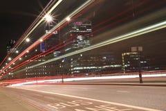 Η αστική νύχτα πόλεων πυροβόλησε στη γέφυρα του Λονδίνου, κόκκινο λεωφορείο στην κίνηση, μακρύς πυροβολισμός έκθεσης Στοκ Φωτογραφία