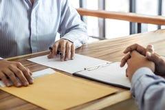 Η ασφάλεια ή η ακίνητη περιουσία δανείου, ο μεσίτης πρακτόρων και ο πελάτης που υπογράφουν το συμφωνητικό σύμβασης που εγκρίθηκε  στοκ φωτογραφία
