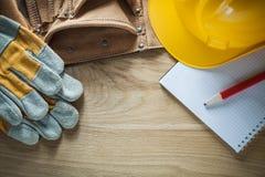Η ασφάλεια ζωνών εργαλείων δέρματος φορά γάντια στο σκληρό μολύβι σημειωματάριων καπέλων Στοκ εικόνες με δικαίωμα ελεύθερης χρήσης