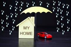 Η ασφάλεια, μια ομπρέλα προστατεύει το σπίτι και το αυτοκίνητο Στοκ φωτογραφίες με δικαίωμα ελεύθερης χρήσης