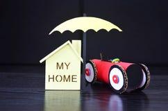 Η ασφάλεια, μια ομπρέλα προστατεύει το σπίτι και το αυτοκίνητο Στοκ Εικόνες