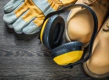 Η ασφάλεια φορά γάντια στα αδιάβροχα λειτουργώντας καλύμματα αυτιών μποτών στον ξύλινο πίνακα Στοκ φωτογραφία με δικαίωμα ελεύθερης χρήσης
