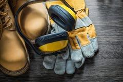 Η ασφάλεια φορά γάντια στα λειτουργώντας καλύμματα αυτιών μποτών στον ξύλινο πίνακα Στοκ Εικόνα