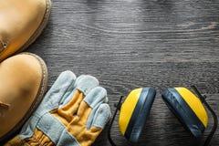 Η ασφάλεια φορά γάντια στα λειτουργώντας καλύμματα αυτιών μποτών δαντελλών στον ξύλινο πίνακα Στοκ φωτογραφίες με δικαίωμα ελεύθερης χρήσης