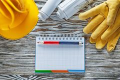 Η ασφάλεια φορά γάντια στο μολύβι σημειωματάριων σχεδιαγραμμάτων κρανών οικοδόμησης Στοκ Φωτογραφίες
