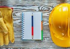 Η ασφάλεια φορά γάντια στο σκληρό μολύβι σημειωματάριων σχεδιαγραμμάτων καπέλων Στοκ φωτογραφία με δικαίωμα ελεύθερης χρήσης