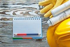 Η ασφάλεια φορά γάντια στο σκληρό μολύβι σημειωματάριων σχεδιαγραμμάτων καπέλων Στοκ εικόνες με δικαίωμα ελεύθερης χρήσης