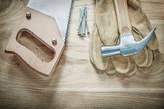 Η ασφάλεια δέρματος σφυριών νυχιών φορά γάντια handsaw στα καρφιά στον ξύλινο πίνακα Στοκ φωτογραφίες με δικαίωμα ελεύθερης χρήσης