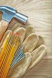 Η ασφάλεια δέρματος φορά γάντια στα ξύλινα καρφιά σφυριών νυχιών μετρητών ξύλινο boa Στοκ φωτογραφία με δικαίωμα ελεύθερης χρήσης