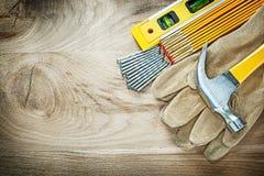 Η ασφάλεια επιπέδων κατασκευής φορά γάντια στα ξύλινα καρφιά σφυριών νυχιών μετρητών Στοκ εικόνα με δικαίωμα ελεύθερης χρήσης