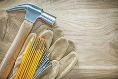 Η ασφάλεια φορά γάντια στα ξύλινα καρφιά σφυριών νυχιών μετρητών στον ξύλινο πίνακα const Στοκ Εικόνα
