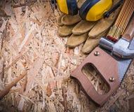 Η ασφάλεια φορά γάντια στα ξύλινα καλύμματα αυτιών σφυριών νυχιών μετρητών handsaw σε OSB Στοκ Εικόνες
