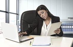 Η λατινική επιχειρησιακή γυναίκα που υφίσταται την πίεση που λειτουργεί στο γραφείο υπολογίζει Στοκ φωτογραφίες με δικαίωμα ελεύθερης χρήσης