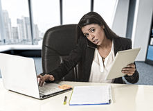 Η λατινική επιχειρησιακή γυναίκα που υφίσταται την πίεση που λειτουργεί στο γραφείο υπολογίζει Στοκ Φωτογραφία