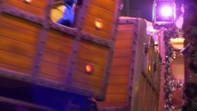 Η ατμομηχανή με τα ξύλινα βαγόνια εμπορευμάτων οδηγά στις ράγες στο υπόβαθρο των φω'των και της διακόσμησης Χριστουγέννων στο βρά απόθεμα βίντεο