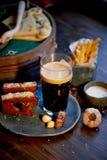 Η ατμόσφαιρα του παλαιού καφέ Ο φορέας με το δίσκο, ένα ποτήρι της σκοτεινής μπύρας, ψωμί σκόρδου και τηγανητά Γρήγορο φαγητό Στοκ Εικόνες
